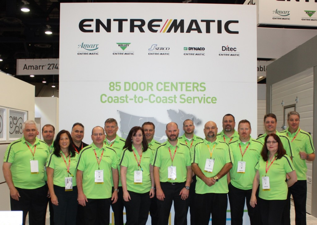 Entrematic Team Members stand by the part of the booth dedicated to our 85 Door Center celebration.